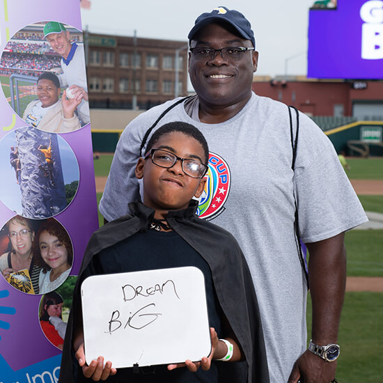 """Big of the Year recipient Jeff """"JB"""" Brown poses with his Little Giovanni. Giovanni is holding a sign that says Dream Big."""