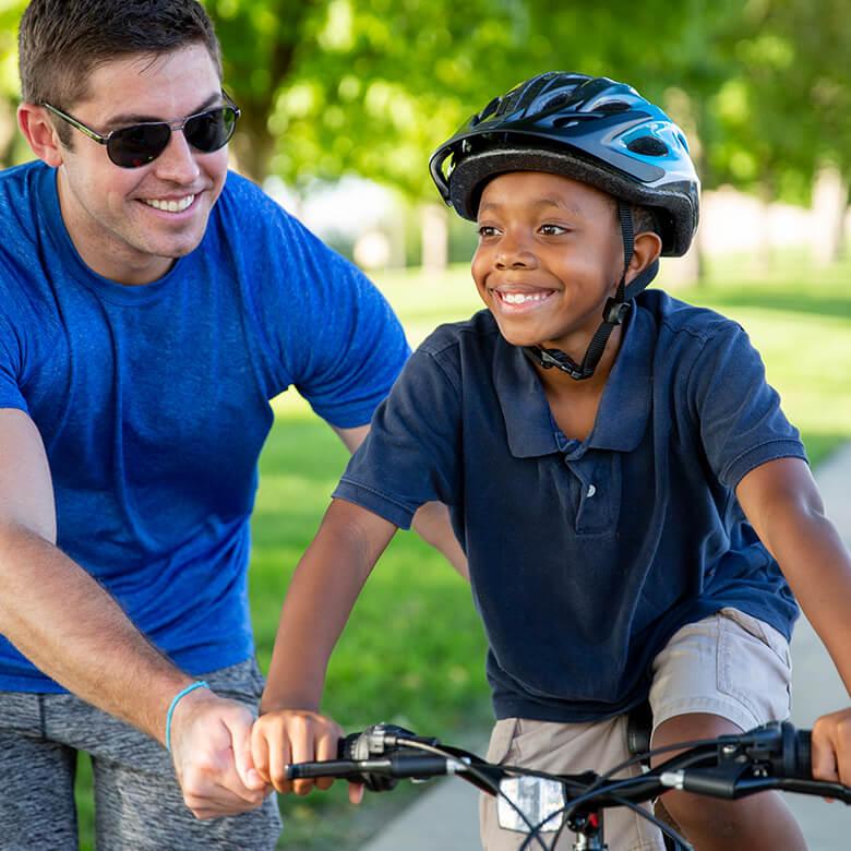 Male Big helping Little ride a bike