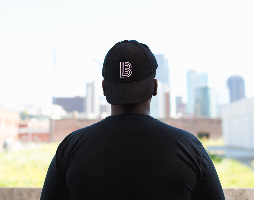 Child with BBBS hat looking at a downtown skyline