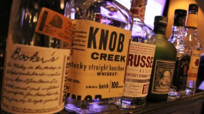 Glass bourbon bottles sitting on a shelf