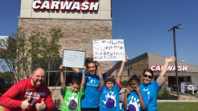 Bigs and Little's at Mike's Car Wash holding signs in support of Big Brothers Big Sisters