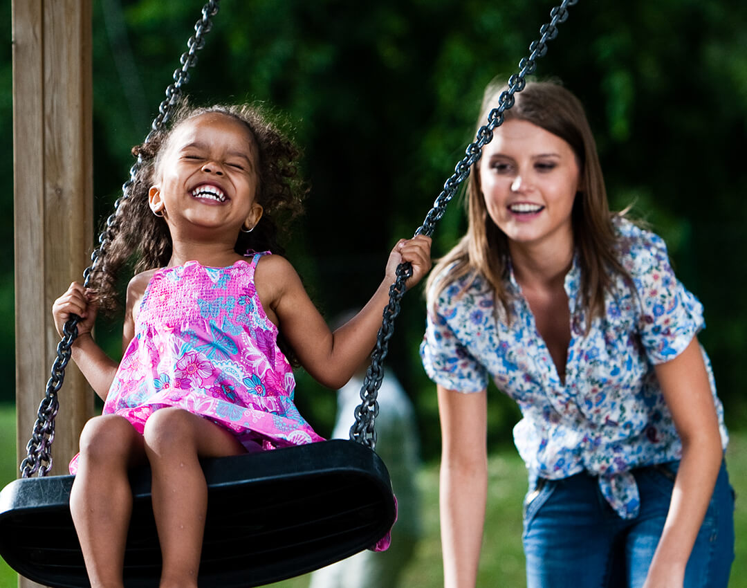 Female Big pushing Little on a swing while she smiles